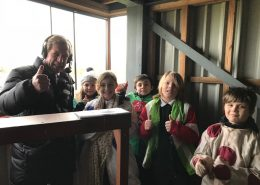Pupils from Fakenham Junior School learning about Sir Peter from Derek Thompson in the commentary box