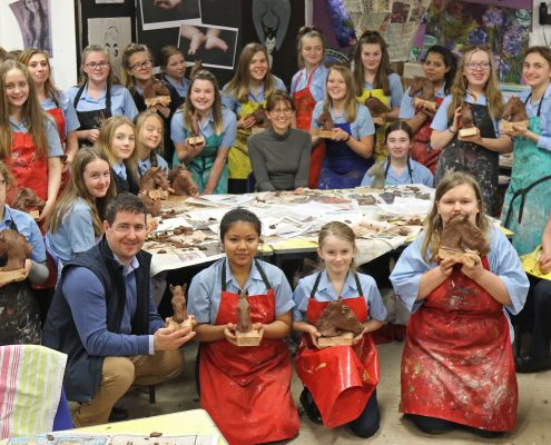 Debbie Burt and Ollie McPhail with the pupils from Newmarket Academy and their finished sculptures