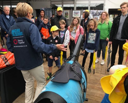 Racing to School's Judith Allen gives potential future champions a demonstration on the Equicizer